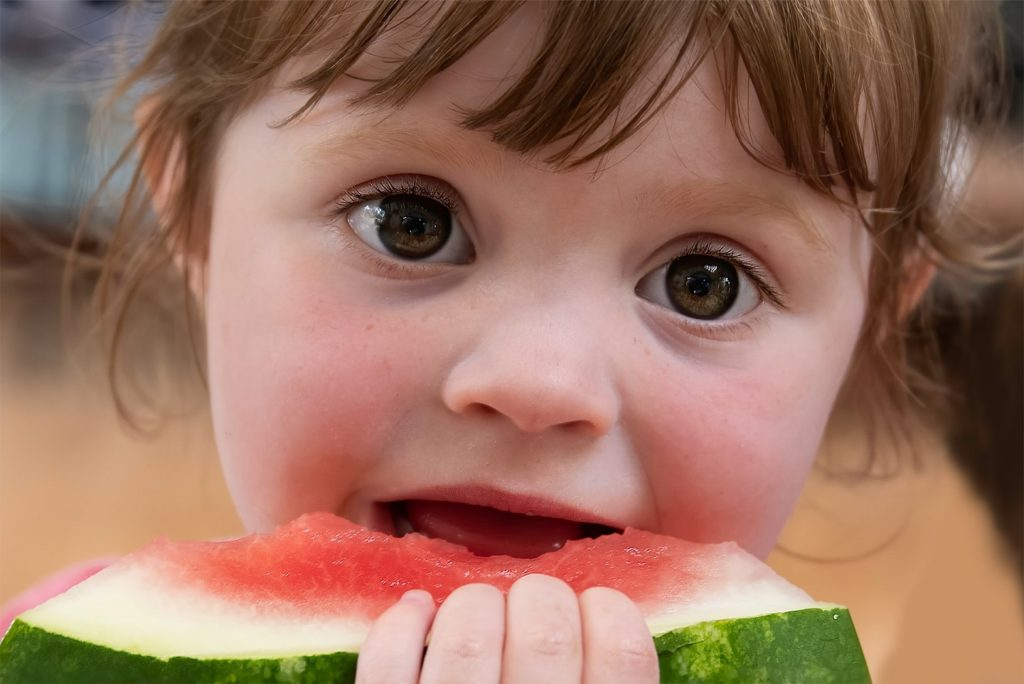 A picture of a child eating a piece of watermelon